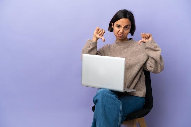 Молодая женщина смешанной расы сидит на стуле с ноутбуком, изолированным на фиолетовом фоне, показывает палец вниз двумя руками