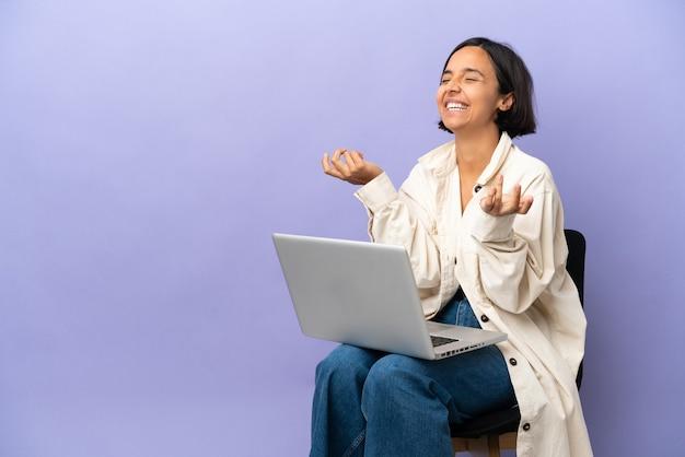 紫の背景に分離されたラップトップと椅子に座っている若い混血の女性