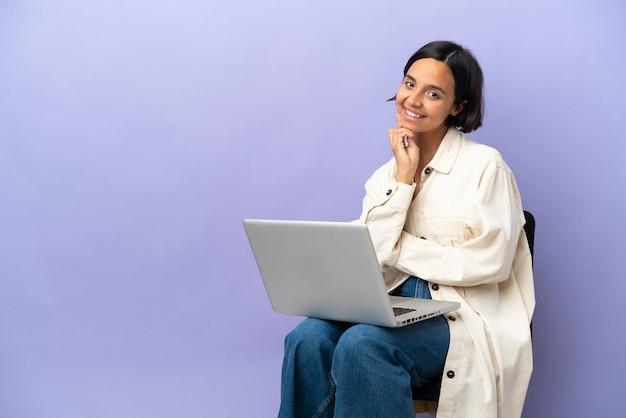 행복하고 즐거운 표정으로 웃고 보라색 배경에 고립 된 노트북과 의자에 앉아 젊은 혼혈 여자