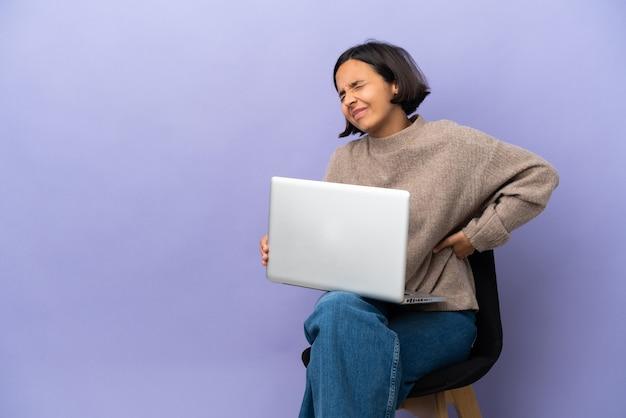 Молодая женщина смешанной расы сидит на стуле с ноутбуком, изолированным на фиолетовом фоне, страдает от боли в спине из-за того, что приложила усилия