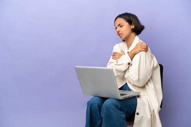 노력을 한 데 대한 어깨 통증으로 고통 보라색 배경에 고립 된 노트북과 의자에 앉아 젊은 혼혈 여자