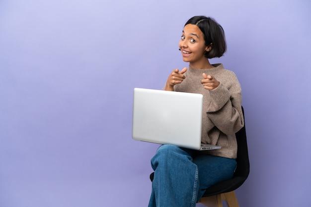 Молодая женщина смешанной расы, сидящая на стуле с ноутбуком, изолирована на фиолетовом фоне, удивлена и указывает вперед