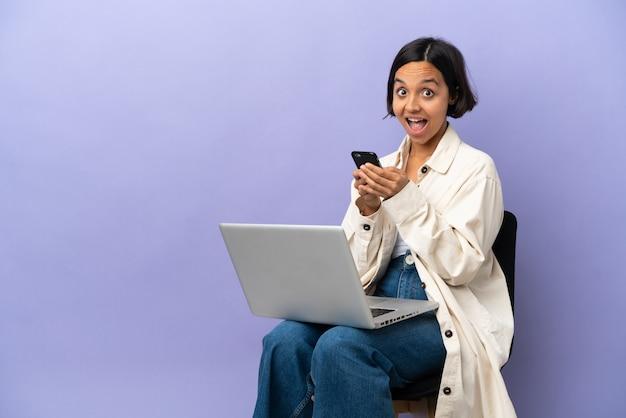 Молодая женщина смешанной расы, сидящая на стуле с ноутбуком, изолированным на фиолетовом фоне, удивлена и отправляет сообщение