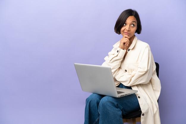 見上げながらアイデアを考えて紫色の背景に分離されたラップトップと椅子に座っている若い混血の女性
