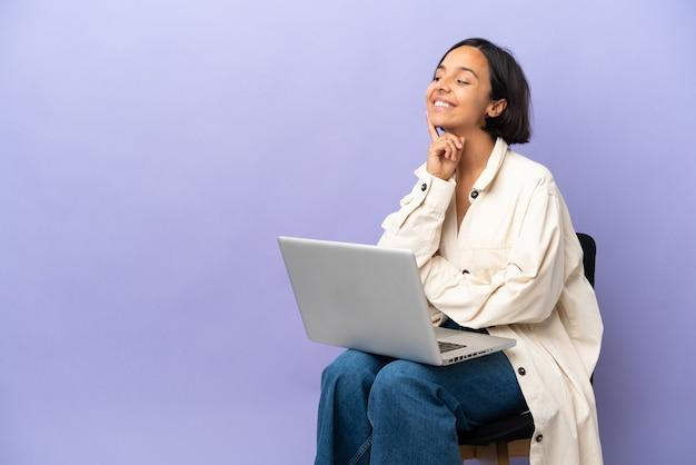 Молодая женщина смешанной расы сидит на стуле с ноутбуком, изолированным на фиолетовом фоне, думая об идее, глядя вверх