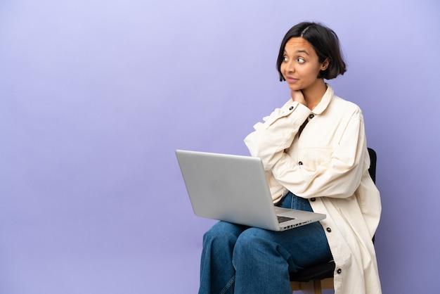 Молодая женщина смешанной расы сидит на стуле с ноутбуком, изолированным на фиолетовом фоне, думая об идее