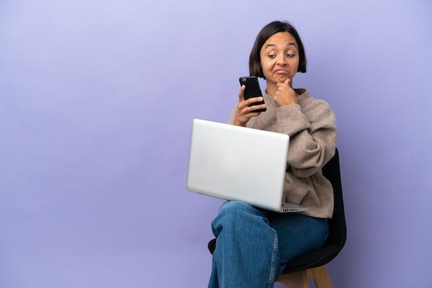 Молодая женщина смешанной расы сидит на стуле с ноутбуком, изолированным на фиолетовом фоне, думает и отправляет сообщение