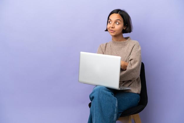 腕を組んで幸せな紫色の背景で隔離のラップトップと椅子に座っている若い混血の女性