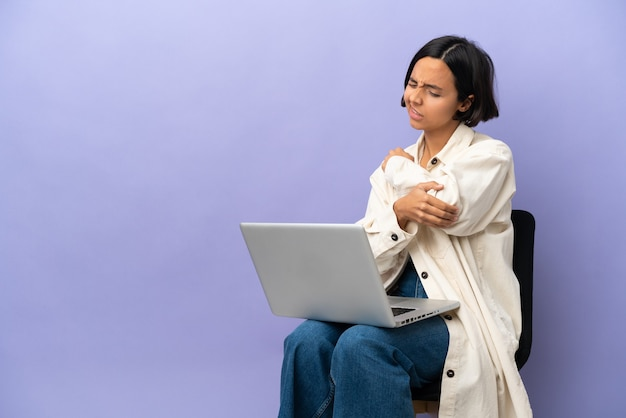 팔꿈치에 통증이 함께 보라색 배경에 고립 된 노트북과 의자에 앉아 젊은 혼혈 여자