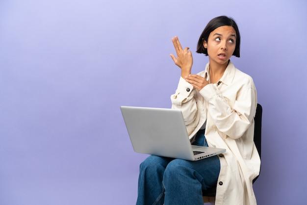 Молодая женщина смешанной расы сидит на стуле с ноутбуком, изолированным на фиолетовом фоне, с проблемами, совершающими жест самоубийства