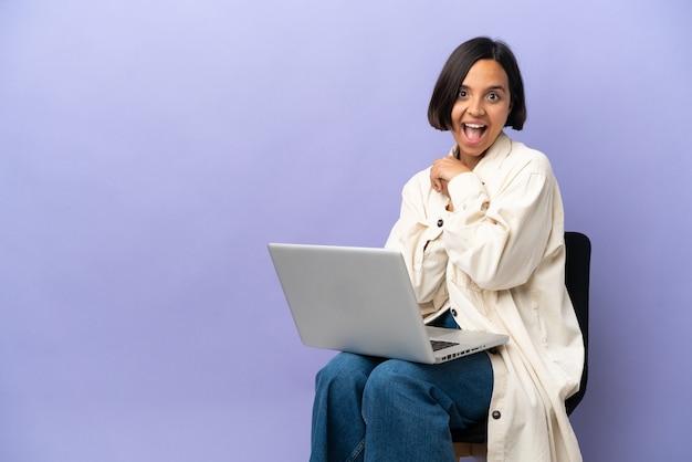 Молодая женщина смешанной расы сидит на стуле с ноутбуком, изолированным на фиолетовом фоне с удивленным выражением лица