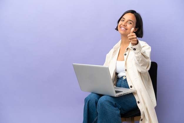 Молодая женщина смешанной расы сидит на стуле с ноутбуком, изолированным на фиолетовом фоне с большими пальцами руки вверх, потому что произошло что-то хорошее