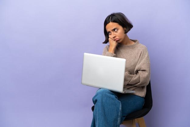 Молодая женщина смешанной расы, сидящая на стуле с ноутбуком, изолирована на фиолетовом фоне с усталым и скучающим выражением лица