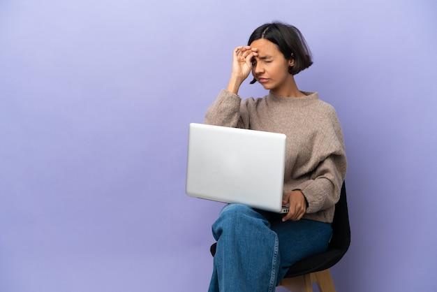 Молодая женщина смешанной расы, сидящая на стуле с ноутбуком, изолирована на фиолетовом фоне с усталым и больным выражением лица