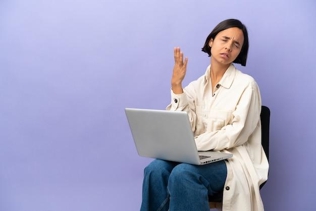 피곤하고 아픈 표정으로 보라색 배경에 고립 된 노트북과 의자에 앉아 젊은 혼혈 여자