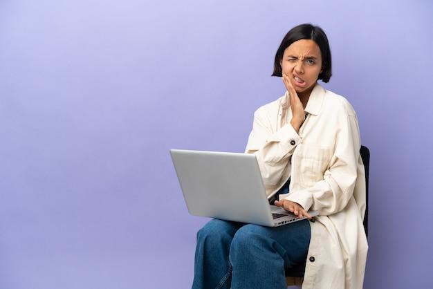 Молодая женщина смешанной расы, сидящая на стуле с ноутбуком, изолирована на фиолетовом фоне с зубной болью