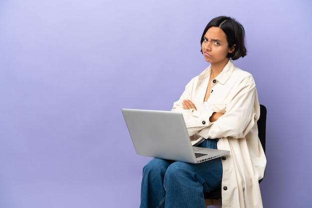 Молодая женщина смешанной расы, сидящая на стуле с ноутбуком, изолирована на фиолетовом фоне с несчастным выражением лица