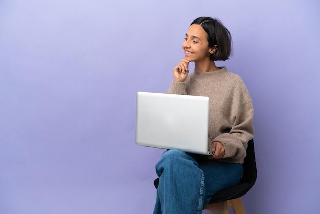 Молодая женщина смешанной расы сидит на стуле с ноутбуком, изолированным на фиолетовом фоне