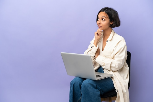 Молодая женщина смешанной расы сидит на стуле с ноутбуком, изолированным на фиолетовой стене и смотрит вверх