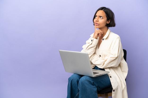 Молодая женщина смешанной расы сидит на стуле с ноутбуком, изолированным на фиолетовой стене, сомневается, глядя вверх