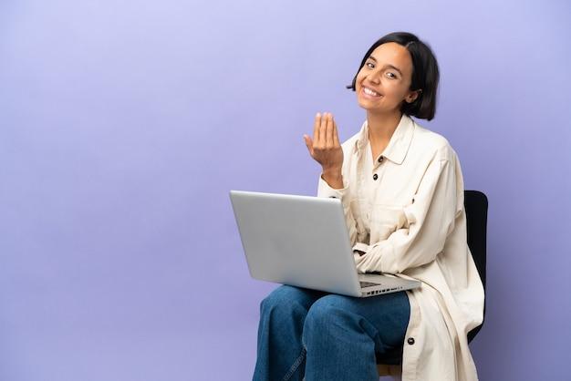 Молодая женщина смешанной расы сидит на стуле с ноутбуком, изолированным на фиолетовой стене, приглашая прийти с рукой. счастлив что ты пришел
