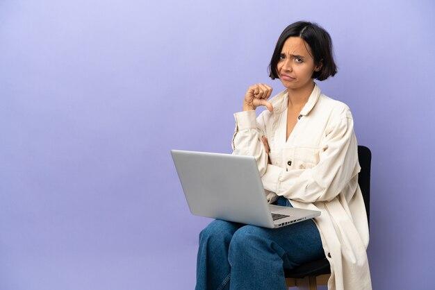 Молодая женщина смешанной расы, сидящая на стуле с ноутбуком, изолирована на фиолетовой стене, показывая большой палец вниз с отрицательным выражением лица