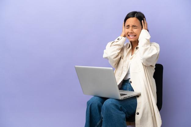 Молодая женщина смешанной расы, сидящая на стуле с ноутбуком, изолирована на фиолетовой стене, подчеркнула подавленность