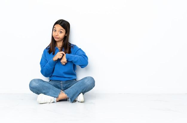 Молодая женщина смешанной расы, сидя на полу, изолированных на белой стене, делая жест опоздания