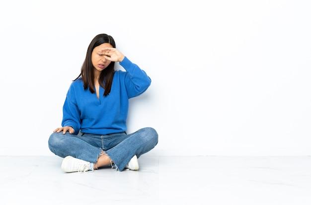 Молодая женщина смешанной расы, сидящая на полу