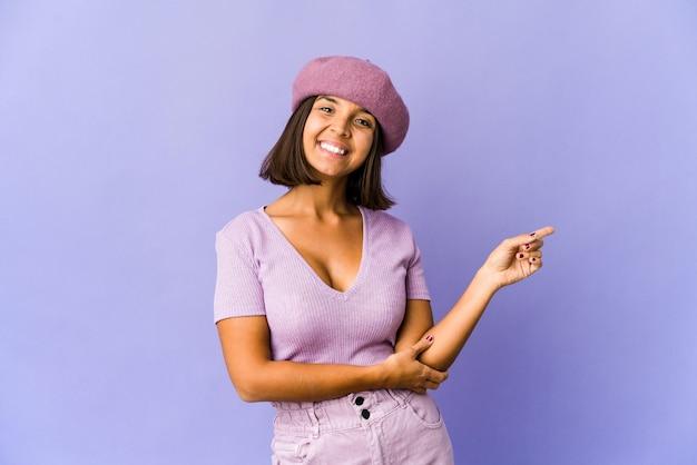 Молодая женщина смешанной расы, весело улыбаясь, указывая указательным пальцем.