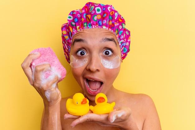 スポンジとゴム製のアヒルを持って入浴している若い混血の女性