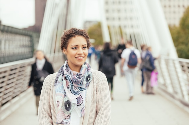 Young mixed race woman walking on a bridge in london