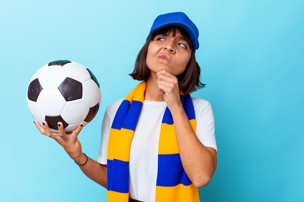 Young mixed race woman watching soccer isolated on blue background looking sideways with doubtful and skeptical expression.