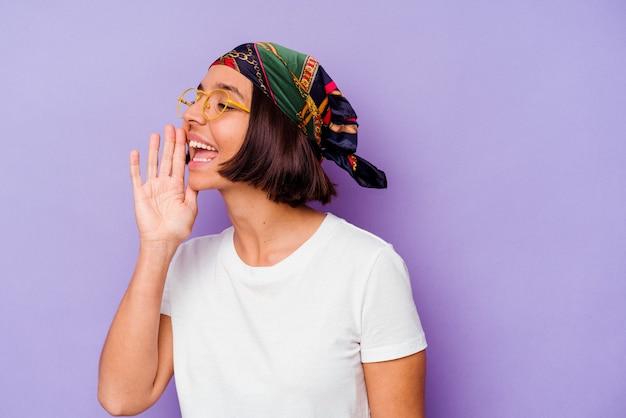 보라색 배경 소리와 열린 된 입 근처에 손바닥을 들고에 고립 된 두건을 입고 젊은 혼합 된 인종 여자.