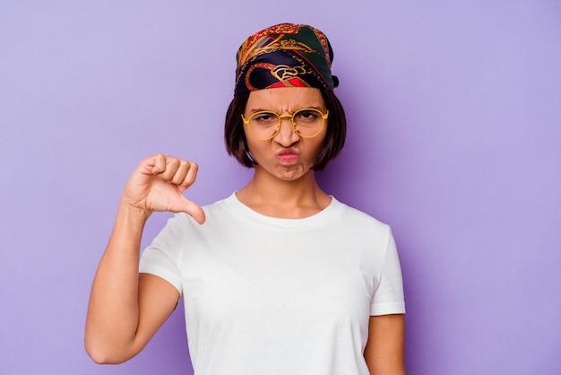 싫어하는 제스처, 엄지 손가락을 보여주는 보라색 배경에 고립 된 두건을 입고 젊은 혼합 된 인종 여자. 불일치 개념.