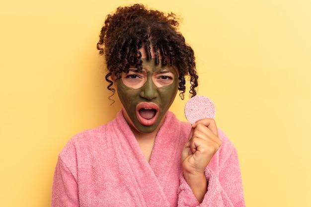 Молодая женщина смешанной расы, носящая халат, держащая губку для снятия макияжа, изолированную на желтом фоне, кричала очень сердито и агрессивно.