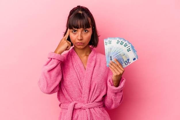 ピンクの背景に指で寺院を指して、考えて、タスクに焦点を当てて分離された請求書を保持しているバスローブを着ている若い混血の女性。