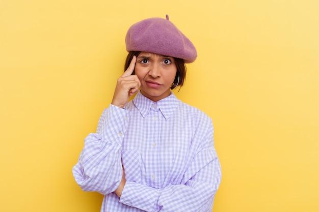 Молодая женщина смешанной расы в берете, изолированном на желтом фоне, сосредоточилась на задаче, держа указательные пальцы, указывая головой.