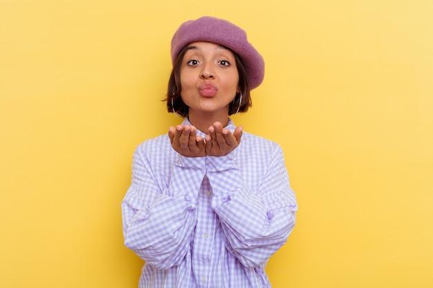 공기 키스를 보내려면 입술을 접고 손바닥을 들고 노란색 배경에 고립 된 베레모를 입고 젊은 혼합 된 인종 여자.
