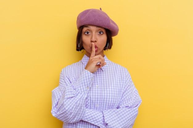 비밀을 유지하거나 침묵을 요구하는 노란색 벽에 고립 된 베레모를 입고 젊은 혼합 된 인종 여자.