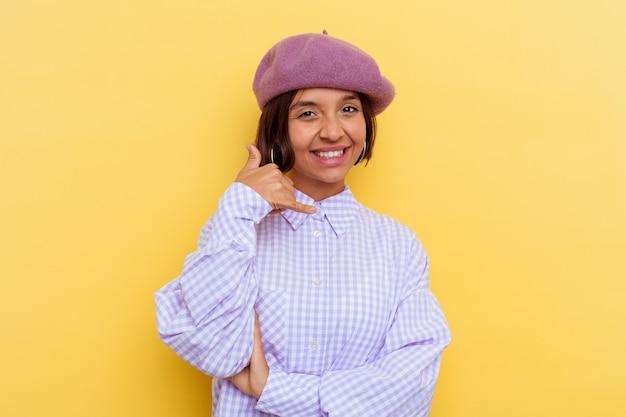 指で携帯電話の呼び出しジェスチャーを示す黄色の壁に分離されたベレー帽を身に着けている若い混血の女性。