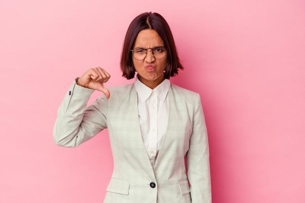 Молодая женщина смешанной расы в зеленом костюме на розовой стене показывает жест неприязни и показывает палец вниз