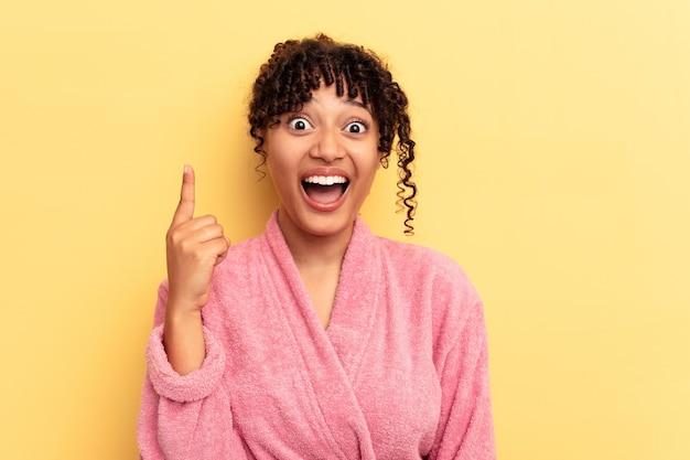 アイデア、インスピレーションのコンセプトを持つピンクの背景に分離されたピンクのバスローブを着ている若い混血の女性。