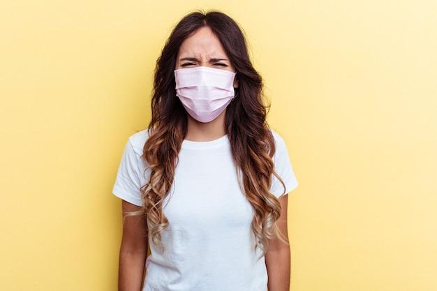 Молодая женщина смешанной расы, носящая защиту от вируса, изолированную на желтом фоне