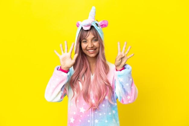 Молодая женщина смешанной расы в пижаме с единорогом на белом фоне считает девять пальцами
