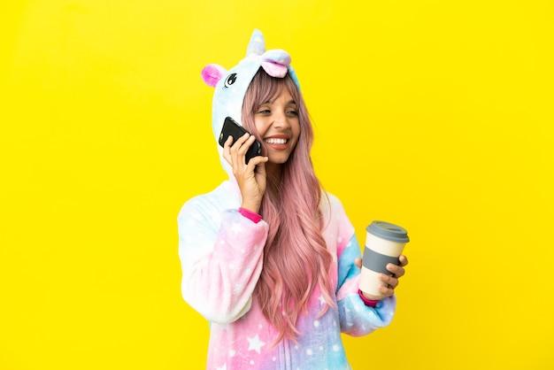 Молодая женщина смешанной расы в пижаме единорога на белом фоне держит кофе на вынос и мобильный