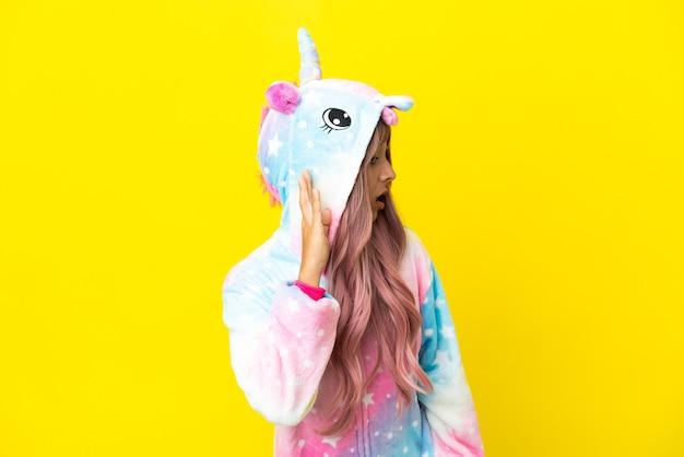 Молодая женщина смешанной расы в пижаме с единорогом на белом фоне слушает что-то, положив руку на ухо