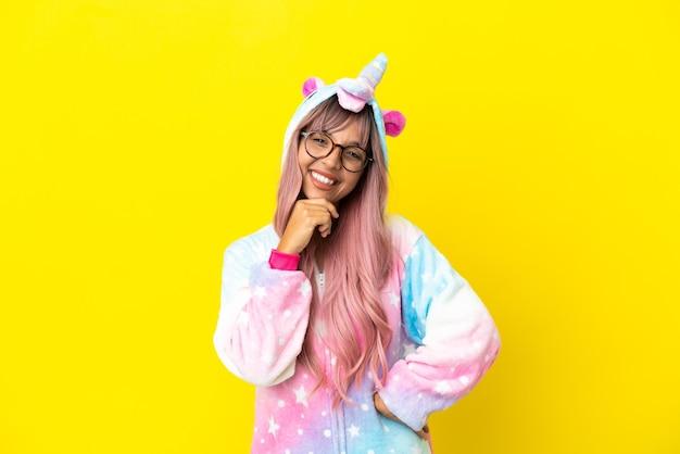 眼鏡と笑顔で白い背景で隔離のユニコーンパジャマを身に着けている若い混血の女性