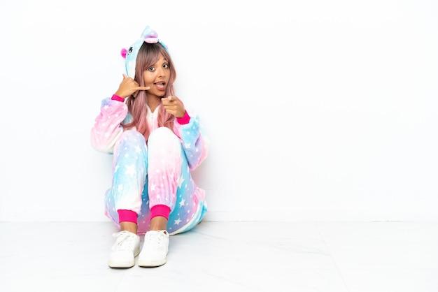 白い背景で隔離の床に座っているユニコーンのパジャマを身に着けている若い混血の女性は、電話のジェスチャーをし、正面を指しています
