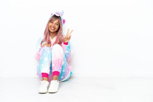 Молодая женщина смешанной расы в пижаме с единорогом сидит на полу, изолированном на белом фоне, улыбается и показывает знак победы